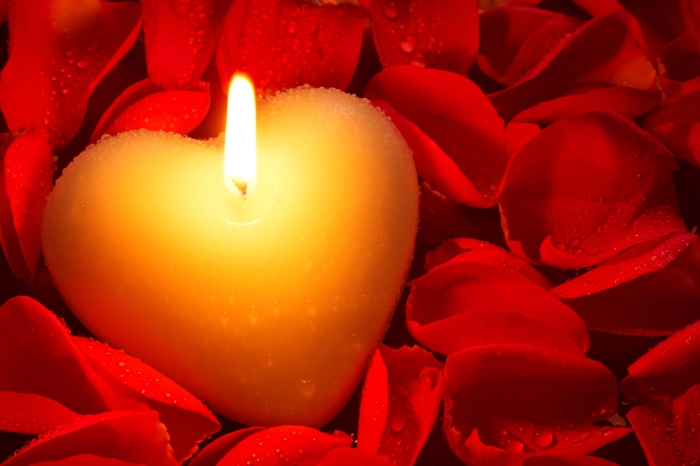 A heart shape candle surrounded by red rose petals covered in wa